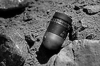 """PARWAN PROVINCE, AFGHANISTAN - MAY 19, 2012.  .A 40 mm live grenade lies on the sandy grounds of the East River Firing range in Bagram district. Even though this area is technically off-limits to the local villagers, there are no visible warning signs in Dari or Pashto, the two most prominent languages in Afghanistan. Moreover, the lack of adequate pasturing grounds for the local goat herders make it an economic necessity for them to cross over to the greener pastures that surround the firing range. ..In addition, what the local de-mining teams call """"scrappies"""" - children who collect shrapnel and scrap metal to sell - walk into this firing range  to look for items such as rocket parts, bullet casings and other metal parts, are as a result, are being injured when they encounter live rounds (old soviet anti-personel mines and current 40 mm grenades used by the armed forces out of Bagram airbase when they conduct training on these grounds).  (Javier Manzano / For The Washington Post). .."""