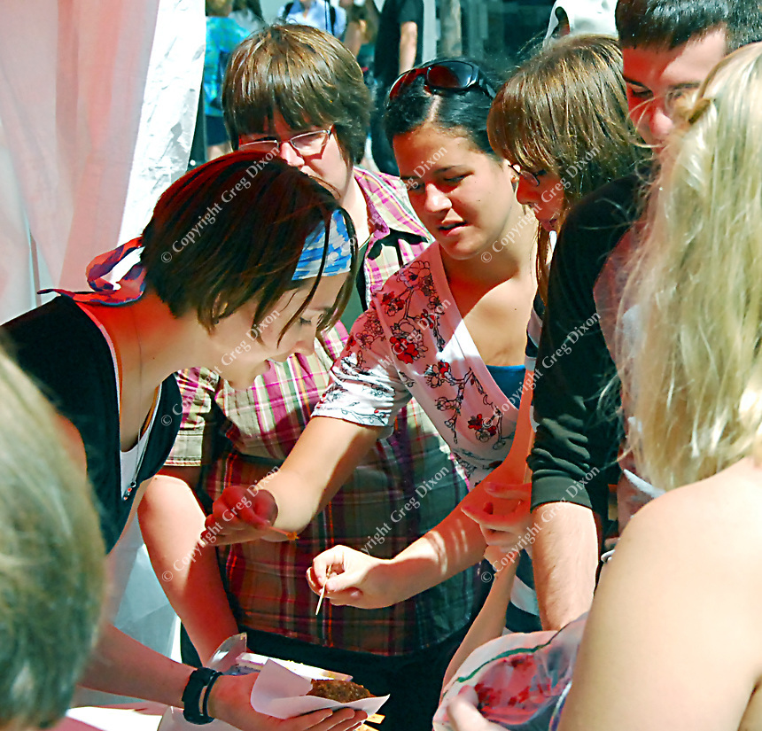 Grace Cheesecakes employee, Rachael Weiker (left), serves samples at the Dane County Farmer's Market on Saturday, July 25, 2009