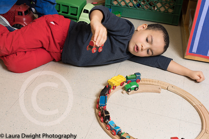 Education Preschool 3-4 year olds boy playing by himself with wooden train set talking to himself