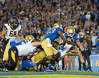 Daniel Lasco of California runs the ball into an end zone to score a touchdown during the game against UCLA at Rose Bowl in Pasadena, California on October 12th, 2013.   UCLA defeated California, 37-10.