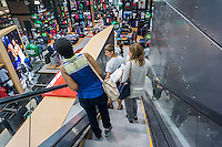 Shoppers on an escalator in the new Dick's Sporting Goods store in Valley Stream, Long Island, New York during its grand opening sales on Saturday, July 9, 2016. Dick's recently purchased the intellectual property of its bankrupt competitor Sports Authority with a $15 million bid pending the courts' final approval on July 15.   (© Richard B. Levine)