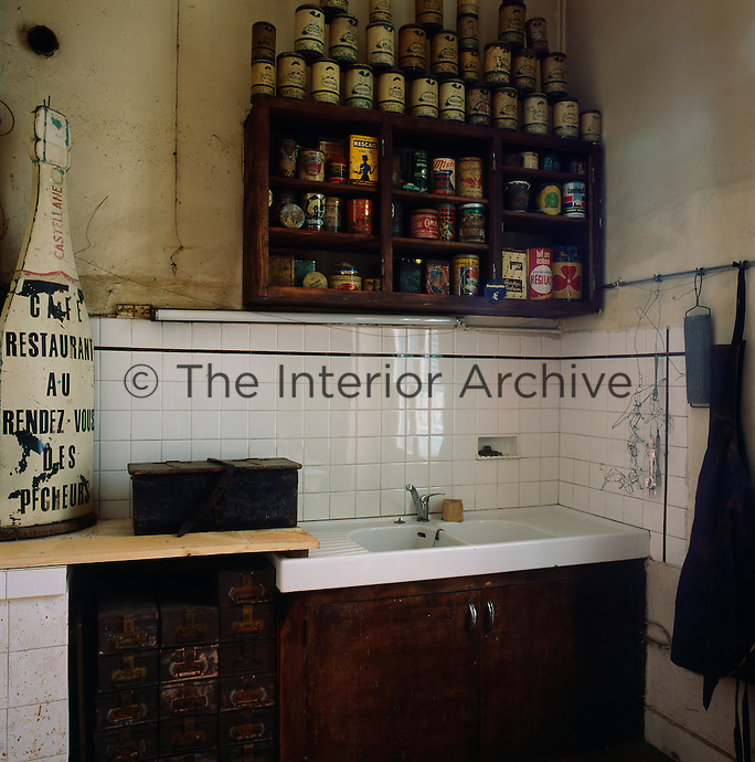 A traditional kitchen with a basic sink arrangement in one corner against a white tiled wall. Above the sink, a collection of food products and vintage storage tins on wooden shelving provides an interesting feature.