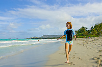 A girl runs playfully on Kailua Beach.
