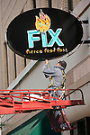A Yesco worker fixes the FIX (Fierce Food Fast) restaurant sign, Central Avenue, old Rt. 66 through downtown Albuquerque, New Mex.