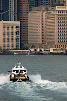 Tugboat crossing Victoria Harbour in the morning, with Kowloon skyscrapers in the background, Hong Kong Island, Hong Kong, China.