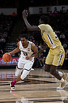 Bryant Crawford (13) of the Wake Forest Demon Deacons drives past Abdoulaye Gueye (34) of the Georgia Tech Yellow Jackets during second half action at the LJVM Coliseum on February 14, 2018 in Winston-Salem, North Carolina.  The Demon Deacons defeated the Yellow Jackets 79-62.  (Brian Westerholt/Sports On Film)