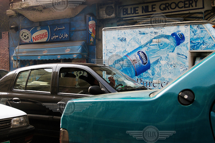 Delivery truck for Nestle bottled water outside shop with awning also advertising Nestle products.