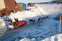 Paul Gebhart runs down a ramp and onto the Unalakleet slough ice after leaving Unalakleet in Arctic Alaska during the 2010 Iditarod