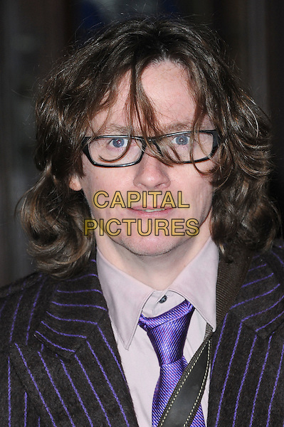 Ed Byrne.The Prince's Trust Comedy Gala, Royal Albert Hall, London, England..28th November 2012.headshot portrait white shirt purple tie black pinstripe glasses   .CAP/BEL.©Tom Belcher/Capital Pictures.