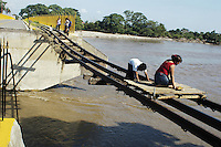 Guatemalan woman crossing the border illegaly to Mexico on a makeshift cart.  Only the railroad tracks remain over this part of the bridge which was washed away by the Suchiate river during huricane Stan.