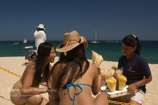 Female beach vendor showing her goods to tourists on the beach (playa), Cabo San Lucas, Baja California, Mexico