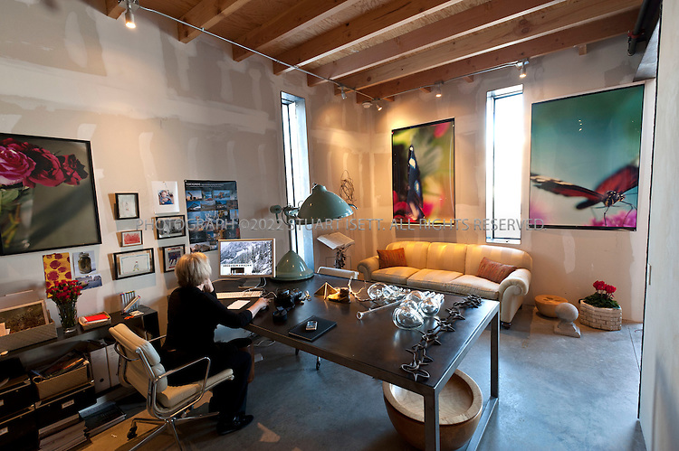 """12/19/2008--Bellevue, Idaho, USA..Ground floor office.The Outpost, owned by Jan Cox. The office is decorated with large photos by Ms. Cox (shown at her desk). Ms. Cox, whose father was an architect, first came to Idaho's Wood River Valley on a ski trip as a child...Set in the remote and harsh high desert landscape of Idaho, Outpost is a residence and studio/workshop for making and displaying art. An important aspect of the complex is the protected """"paradise garden,"""" which is separated from the wild landscape by thick concrete walls. The materials used in the structure, including concrete block, car-decking, and plywood, require little or no maintenance, and are capable of withstanding the extreme weather that characterize the desert's four seasons...LEAD ARCHITECT: Tom Kundig of Olson Sundberg Kundig Allen Architects in Seattle, WA...©2008 Stuart Isett. All rights reserved."""