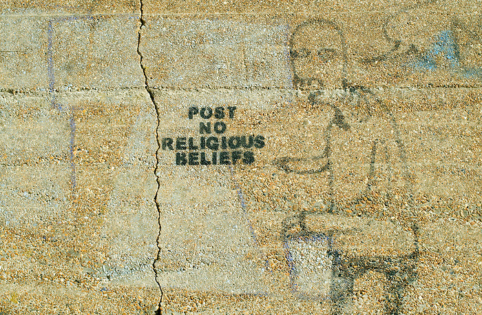 'POST NO RELIGIOUS BELIEFS' - Graffiti on a pebble-dashed sea wall at Shoreham Port, near Brighton, Sussex. England 2008.