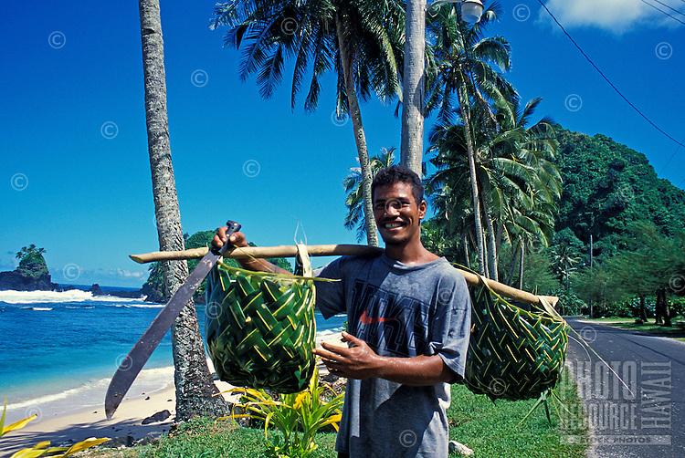 Man carries baskets. Failolo, Tutuila, American Samoa