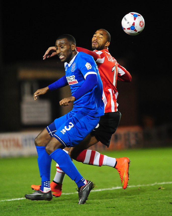 Lincoln City's Delano Sam-Yorke vies for possession with Alfreton Town's Lathaniel Rowe-Turner<br /> <br /> Photo by Chris Vaughan/CameraSport<br /> <br /> Football - FA Challenge Cup Fourth Qualifying Round replay - Lincoln City v Alfreton Town - Tuesday 28th October 2014 - Sincil Bank - Lincoln<br /> <br /> &copy; CameraSport - 43 Linden Ave. Countesthorpe. Leicester. England. LE8 5PG - Tel: +44 (0) 116 277 4147 - admin@camerasport.com - www.camerasport.com