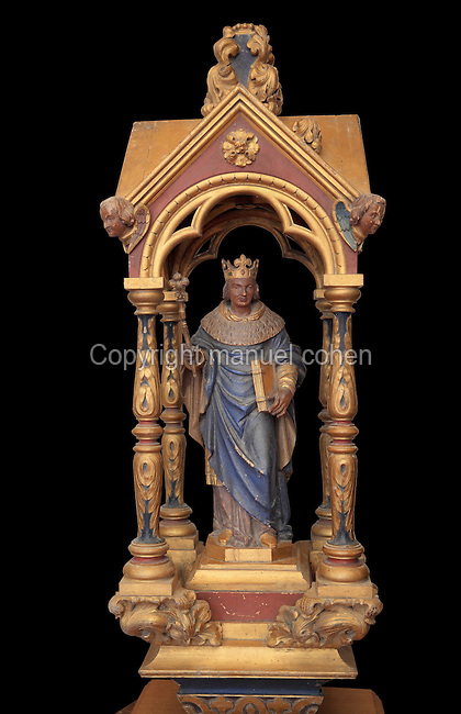 Polychrome carved figure of Saint Louis under a neogothic canopy from a processional sceptre, 1820-50, in the Collegiale Notre-Dame de Poissy, a catholic parish church founded c. 1016 by Robert the Pious and rebuilt 1130-60 in late Romanesque and early Gothic styles, in Poissy, Yvelines, France. Saint Louis wears the fleur de lys crown and holds a sceptre and a book, possibly a Book of Trades which he commissioned. The Collegiate Church of Our Lady of Poissy was listed as a Historic Monument in 1840. Picture by Manuel Cohen