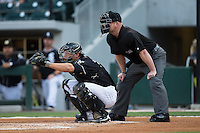 Charlotte Knights catcher Kevan Smith (32) catches a pitch as home plate umpire Jonathan Bailey looks over his shoulder during the game against the Norfolk Tides at BB&T BallPark on April 20, 2016 in Charlotte, North Carolina.  The Knights defeated the Tides 6-3.  (Brian Westerholt/Four Seam Images)