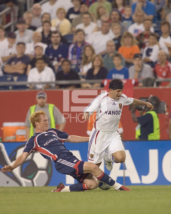 Jeff Larentowicz (Revolution, blue) with a hard tackle on Alecko Eskandarian (Real Salt Lake, white). New England Revolution played Real Salt Lake to a 0-0 tie, at Gillette Stadium on June 2, 2007.