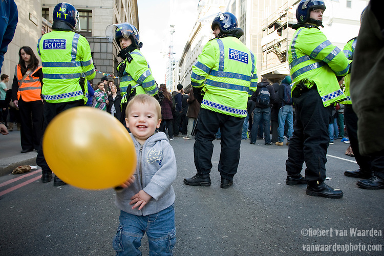 A young camper plays with a balloon while police officers maintain an eye on the crowd.