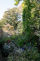 The garden surrounding the restored barn is full of flowering plants