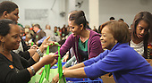 First Lady Michelle Obama and Sasha and her mother, Marion Robinson fill bags with produce at the Capital Area Food Bank in North East Washington DC on November 23, 2011. Malia Obama is at far right..Credit: Dennis Brack / Pool via CNP