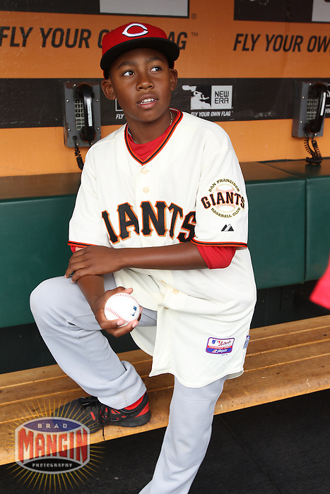 SAN FRANCISCO, CA - JULY 1:  Darren Baker, son of Manager Dusty Baker #12 of the Cincinnati Reds wears a San Francisco Giants jersey in the dugout before on field ceremonies honoring the Giants 2002 National League Championship team that Baker managed. Darren Baker later threw out the first pitch before the game against the San Francisco Giants at AT&T Park on Sunday, July 1, 2012 in San Francisco, California. Photo by Brad Mangin