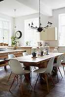 A large chandelier hangs over the dining table, surrounded by Eames chairs. The kitchen worktop made from English maple dominates. A retro clock by Smith + Co hangs in the corner above cut hydrangeas.