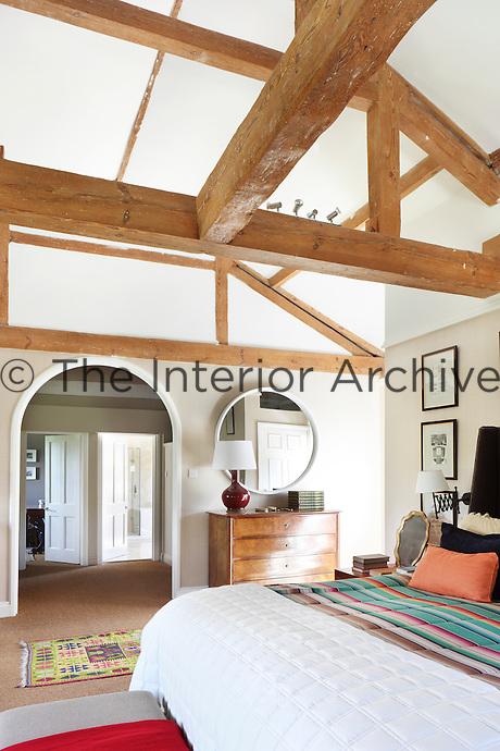 A lofty master bedroom with exposed rafters and natural sisal flooring