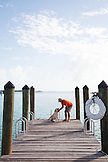 EXUMA, Bahamas. Yves and resident dog, Ruby, hanging out on the dock of the Fowl Cay Resort.