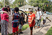 """Sheryl Bostic is consoled by Dean Padgett as onlookers pray. Kwame Smith guards Dean's cross. """"The greatest sin is doing nothing, it's the greatest selfishness of all,"""" he says of people who are indifferent to the plight of others."""