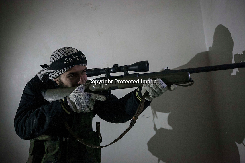 In this Tuesday, Dec. 11, 2012 photo, a Syrian rebel sniper aims toward troops loyal to President Bashar al-Assad during clashes in Aleppo, Syria. (AP Photo/Narciso Contreras)