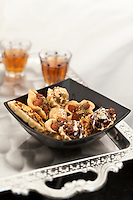 Detail of a bowl of Middle Eastern sweet biscuits and glasses of tea on a silver tray