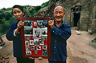 September, 1985. Shaanxi Province, China. Older generation villagers showing photos of their family members who participated with Mao Zedong in the Long March.