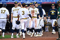 Michigan Wolverines outfielder Cody Bruder (3) greeted by teammates including Eric Jacobson (12) after scoring a run during the first game of a doubleheader against the Siena Saints on February 27, 2015 at Tradition Field in St. Lucie, Florida.  Michigan defeated Siena 6-2.  (Mike Janes/Four Seam Images)