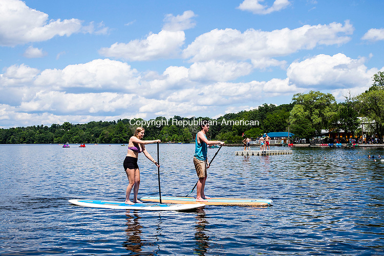 Middlebury, CT- 04 July 2017-070417CM04- Amelia Schill, left, of Newtown and Connor Murphy of Middlebury  coast in on paddle boards at Lake Quassapaug Outing Club in Middlebury on Tuesday.   Guests spent the day swimming, cooking out, fishing, boating and fireworks put on by Lake Quassy Amusement Park.    Christopher Massa Republican-American