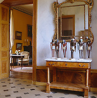 A collection of neo-Egyptian figurines by a contemporary Czech sculptor are displayed on an antique marble-topped side table in the entrance hall