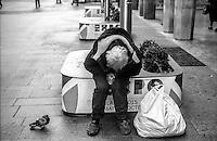 """Milano, corso Vittorio Emanuele, zona centro. Un senzatetto, """"barbone"""", seduto sulla base di una delle bandiere celebrative di Expo 2015 --- Milan, downtown, Vittorio Emanuele street. A homeless sitting on the base of one of the commemorative flags of the Expo 2015"""