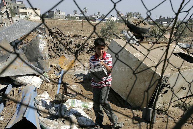 A Palestinian boy walks at the site of an overnight Israeli air raid in Khan Yunis in the southern Gaza Strip on August 20, 2011 on a third day of escalating Israeli-Palestinian tensions. Photo by Abed Rahim Khatib