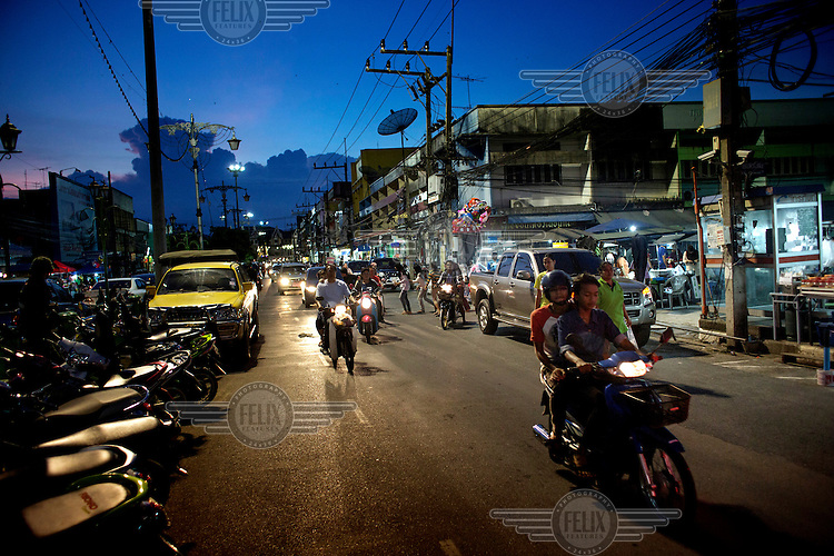 Traffic is seen at dusk in front of the night market close to where a motorbike bomb killed nine year old Nisofian Nisunni and wounded his mother in March this year, in Pattani. /Felix Features