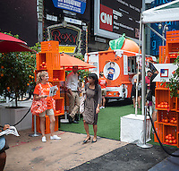 Visitors shop at a JCPenney and Joe Fresh back-to-school promotional event in Times Square in New York on Thursday, August 22, 2013. The retailers created a faux orange grove selling the new Joe Fresh Kids line of children's clothing as part of a back-to-school shopping promotion. One hundred percent of the proceeds from the event are earmarked to go to the JCP Cares Adopt-a-Classroom initiative. JCPenney recently reported a second quarter net loss of $586 million with same store sales down 12 percent.  (© Richard B. Levine)