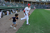 Second baseman Yoan Moncada (24) of the Greenville Drive runs onto the field with a fan in a game against the Greensboro Grasshoppers on Wednesday, August 26, 2015, at Fluor Field at the West End in Greenville, South Carolina. The Cuban-born 19-year-old Red Sox signee has been ranked the No. 1 international prospect in baseball by Baseball America. Greenville won, 7-0. (Tom Priddy/Four Seam Images)