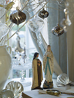 Detail of two figurines from the Nativity beneath a silver sprayed bough adorned with glass baubles