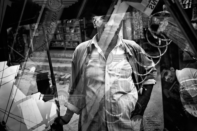 The driver of an auto-rickshaw and a passerby reflected in its windscreen in a street in Hyderbad.