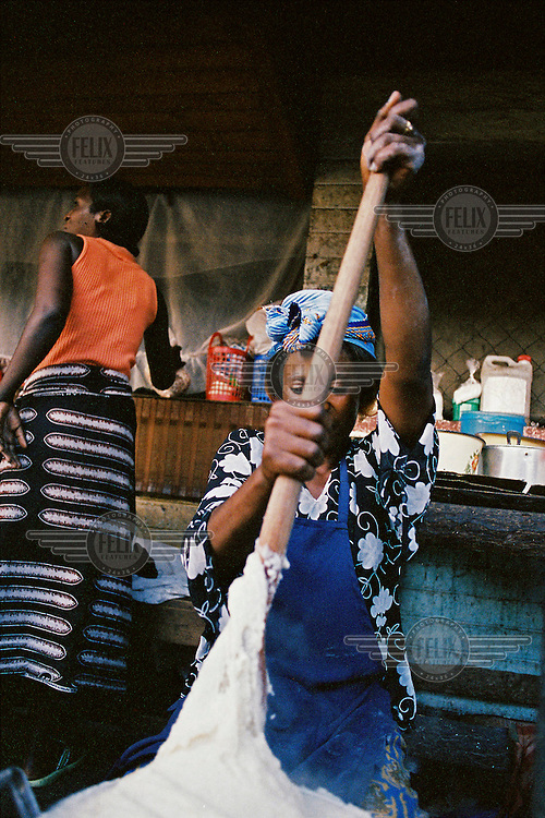 A woman prepares nsima a food staple made from coen meal.
