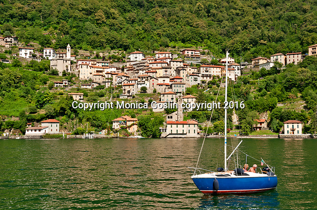 A blue sailboat on Lake Como, Italy with the town of Nesso in the background