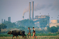 Farmers ploughing field using traditional method next to industrial scene, India.