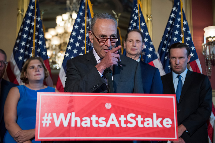 UNITED STATES - JULY 11: Senate Minority Leader Charles Schumer, D-N.Y., and Democratic senators conduct a news conference in the Capitol to oppose the nomination of Brett Kavanaugh to the Supreme Court because they say he would be open to questions about the constitutionality of the Affordable Care Act on July 11, 2018. Also appearing are, from left, Rebecca Wood whose daughter Charlie, 6, was born 3 1/2 months premature, Sens. Ron Wyden, D-Ore., and Chris Murphy, D-Conn. (Photo By Tom Williams/CQ Roll Call)