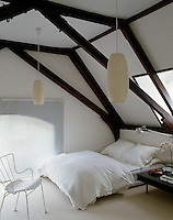 The attic bedroom is simply furnished with angular beams and pendant lights as the dominant feature