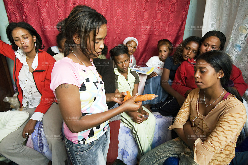 Eritrea. Maekel province. Asmara. Behavioural Change Communication (BCC) for Commercial Sex Workers (CSW). A group of prostitute meet in a small room and talk about HIV Aids prevention. Aids sensibilisation. Wooden orange phallus to show how to use and wear properly a male condom. The Global Fund through the eritrean Ministry of Health supports the programm with a Aids grant (financial aid). © 2006 Didier Ruef
