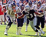 Oakland Raiders vs. San Diego Chargers at Oakland Alameda County Coliseum Sunday, October 11, 1998.  Raiders beat Chargers  7-6.  San Diego Chargers quarterback Ryan Leaf (16) attempts to get away from Oakland Raiders defensive end Lance Johnstone (51).